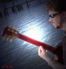 Mark May playin' his guitar on Dickey Bett's dock.